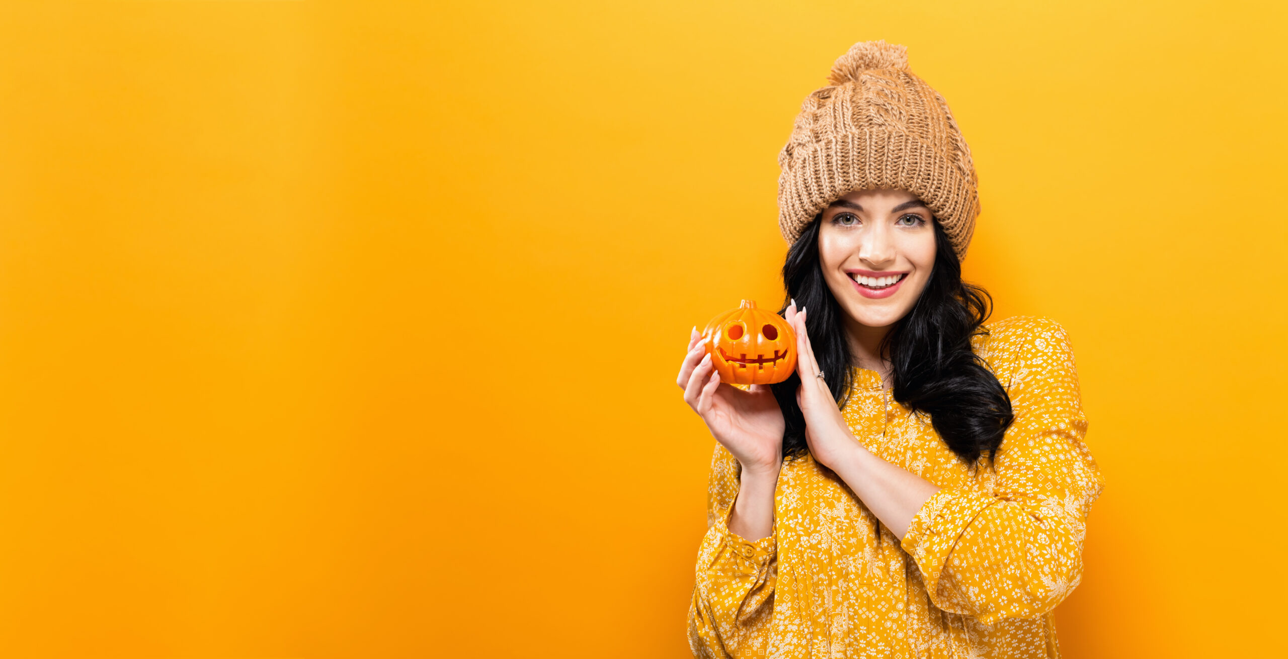 Young woman with a smile holding a pumpkin